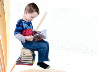 Na zdjęciu chłopiec z ksiązką siedzący na stosie książek