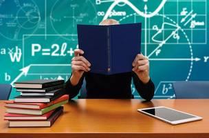 Nauczyciel w klasie za biurkiem trzymający otwarty zeszyt. W tle tablica z wzorami matematycznymi.