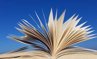 Na zdjęciu na niebieskim tle otwarta ksiażka.