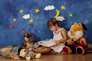 Na zdjęciu dziewczynka z ksiązka na kolanach w otoczeniu pluszowych zabawek