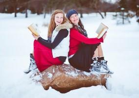 Na zdjęciu dwie młode kobiety z książkami siedzące na kamieniu w zimowej scenerii.