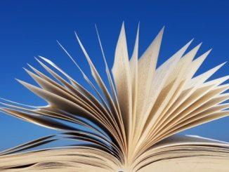 Na zdjęciu otwarta książka na niebieskim tle.