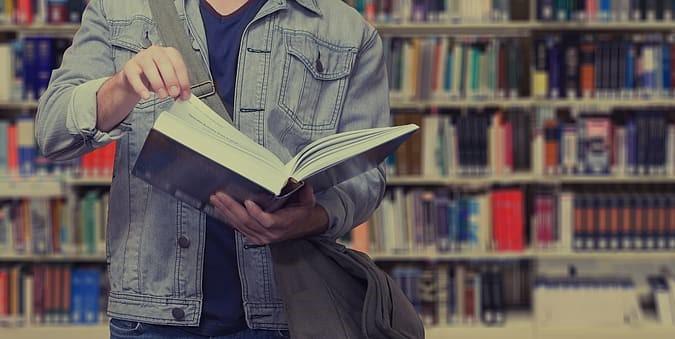 Na zdjęciu student z książką na tle półek z książkami