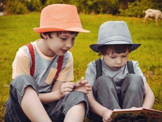 Na zdjaciu dwaj chłopcy w kapeluszach siedzą na łąće. Przed jednym otwarta książka.