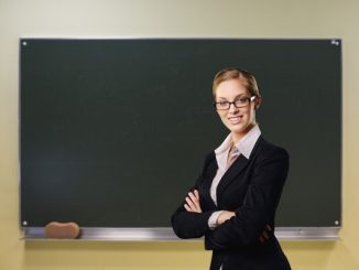 Na zdjęciu kobieta w okularach na tle tablicy szkolnej